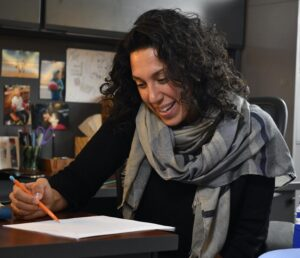 Assistant Professor (Teaching Stream)Malayna Bernstein sitting at a desk and looking at a piece of paper. She is holding a pencil. Her hair is curly and dark brown, and she is wearing a scarf around her neck.